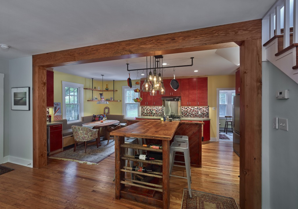 The island was custom fabricated with reclaimed barn wood and the top is made of re-milled antique 2x6 barn floor boards. The legs are antique hand-adzed barn timbers, with a wine rack insert made from antique hay rack spindles.
