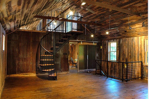 Open-riser central staircase made from reclaimed barn timbers and antique hardware.
